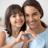Adult and child making heart symbol with hands