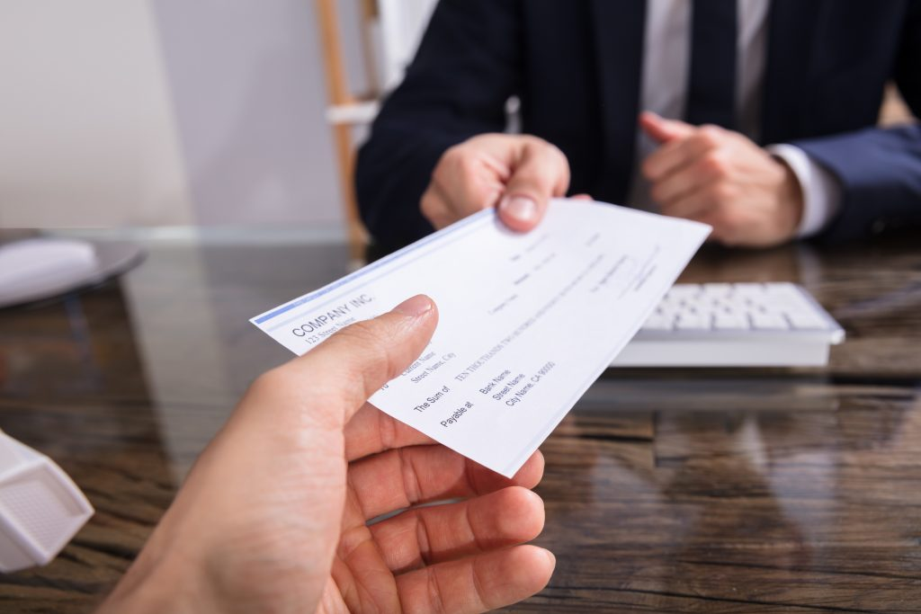 businessperson's hand giving check