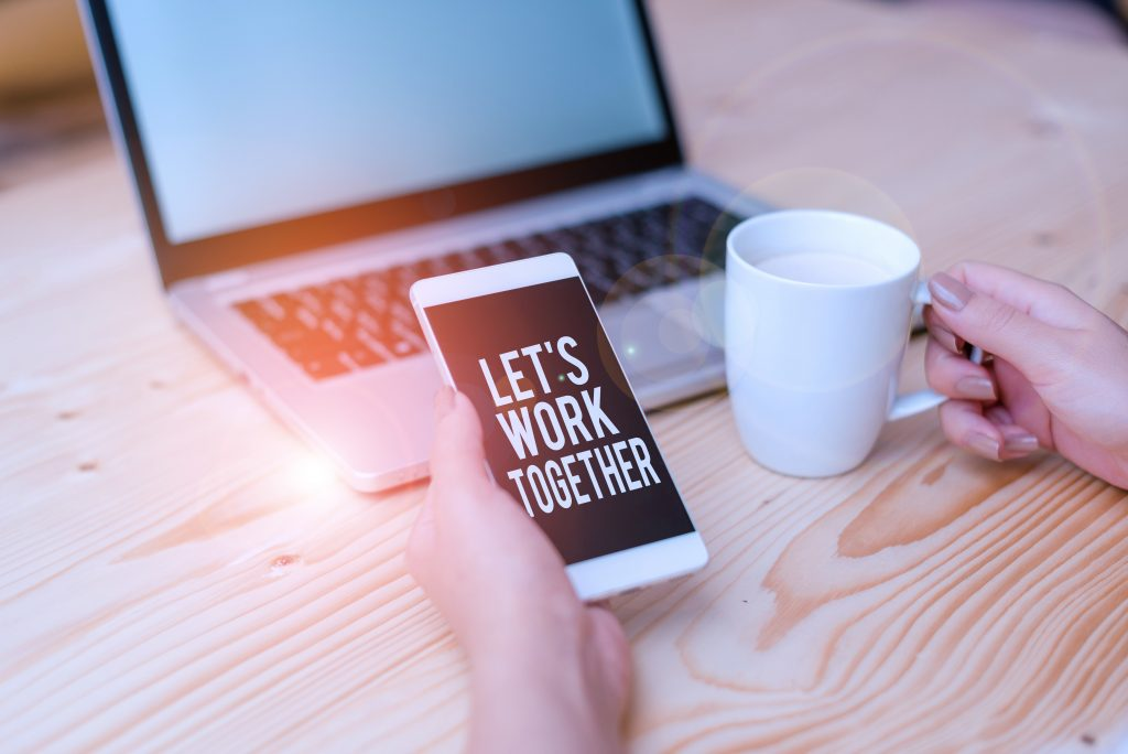 Hand holding phone with let's work together on screen